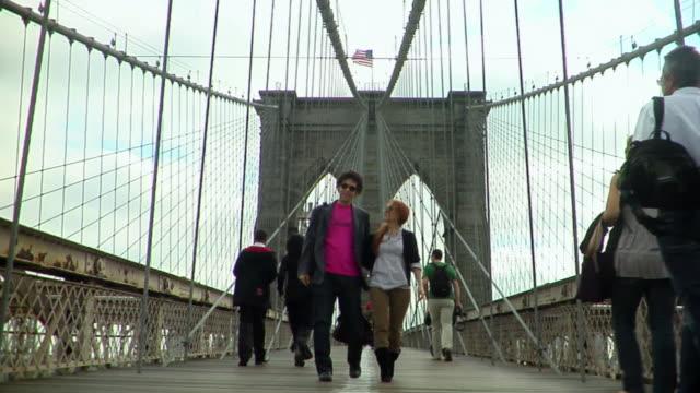ws young couple walk toward camera on the brooklyn bridge/ new york city - hängebrücke stock-videos und b-roll-filmmaterial