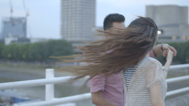 stockvideo's en b-roll-footage met young couple walking across bridge - infaden