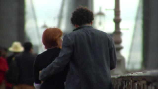 MS Young couple walking across the Brooklyn bridge/ New York City