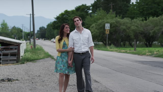 slo mo ws young couple walking along rural road / pleasant grove, utah, usa - mittellanges haar stock-videos und b-roll-filmmaterial