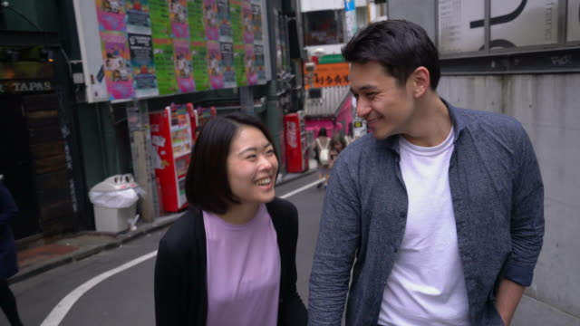 MS Young couple walking along the streets of Tokyo, Japan
