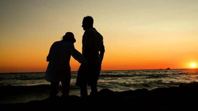 Jong koppel wandelen van het strand in de zonsondergang