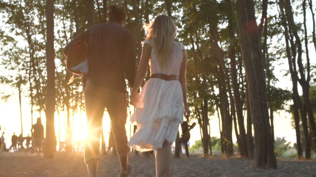 A young couple walking among trees