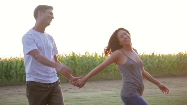 vídeos y material grabado en eventos de stock de young couple walking and holding hands in field - encuadre de tres cuartos