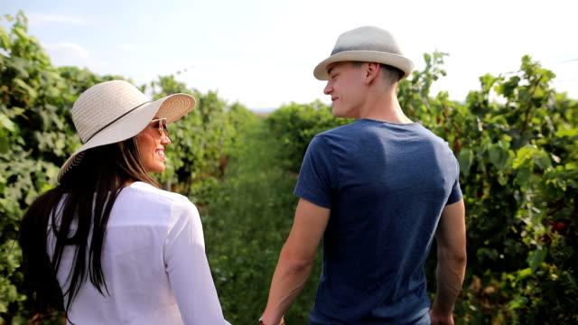 vídeos y material grabado en eventos de stock de pareja joven, paseando por viña hermosa - coquetear