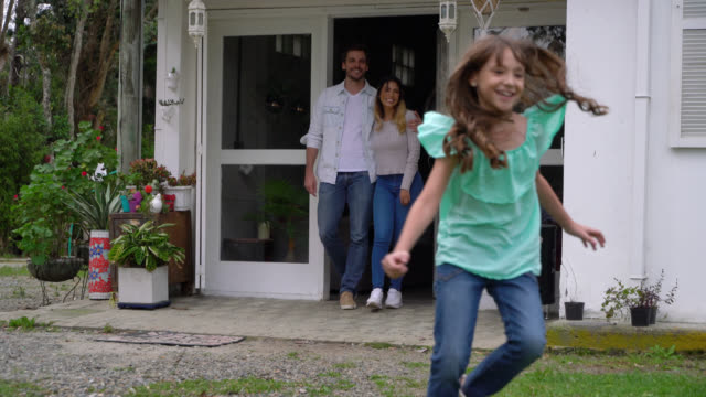 young couple walking behind their kids and dog ready to play while they run out the door to the backyard - facade stock videos & royalty-free footage