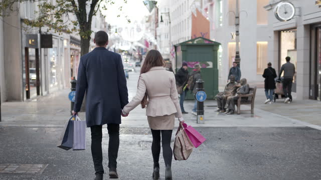 a young couple walking from behind in the city streets christmas shopping - london england stock videos & royalty-free footage