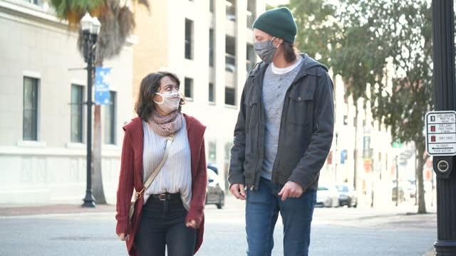 ungt par som går i staden, bär ansiktsmasker - lång längd bildbanksvideor och videomaterial från bakom kulisserna