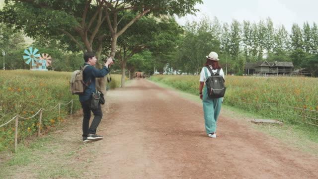 vídeos y material grabado en eventos de stock de joven pareja caminando en la carretera - pareja de mediana edad