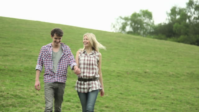 young couple walking in countryside and holding hands - guildford stock videos & royalty-free footage