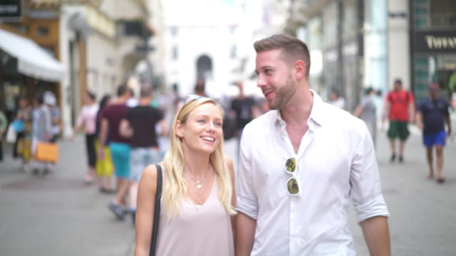 young couple walking in pedestrian zone in city