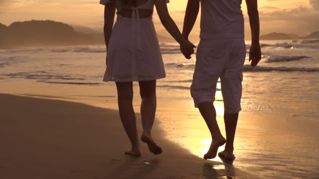 vidéos et rushes de jeune couples marchant dans la plage - rêvasser