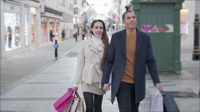 vídeos y material grabado en eventos de stock de una joven pareja caminando por las calles de la ciudad de compras navideñas - escapada urbana
