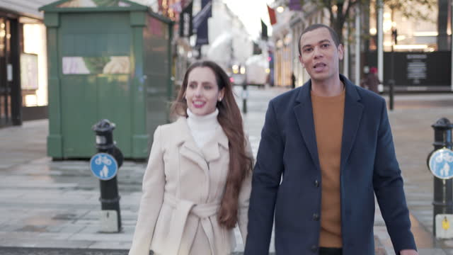 a young couple walking in the city streets christmas shopping - england stock videos & royalty-free footage