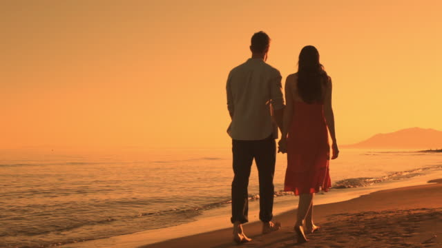 Young couple walking on beach in sunset.