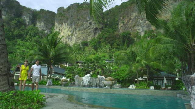 ws young couple walking on poolside of hotel resort in tropical surroundings, krabi, thailand - gemeinsam gehen stock-videos und b-roll-filmmaterial