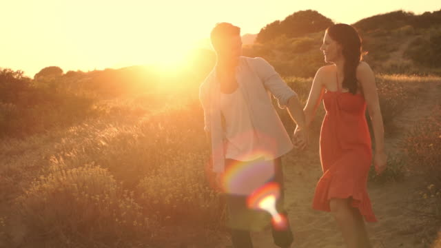 young couple walking on sand dunes in sunset. - 30 39 years stock videos & royalty-free footage