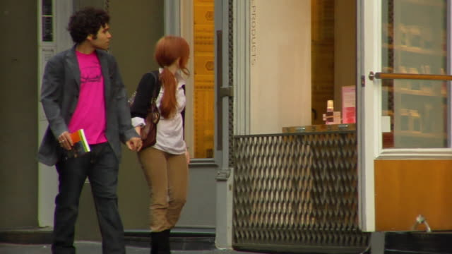 ws pan young couple walking on sidewalk and turning into store/ new york city - entrata video stock e b–roll