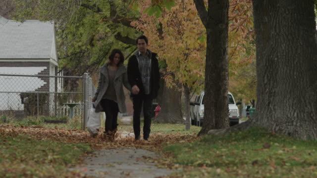 ws pan ms young couple walking on sidewalk in autumn / provo, utah, usa - provo bildbanksvideor och videomaterial från bakom kulisserna