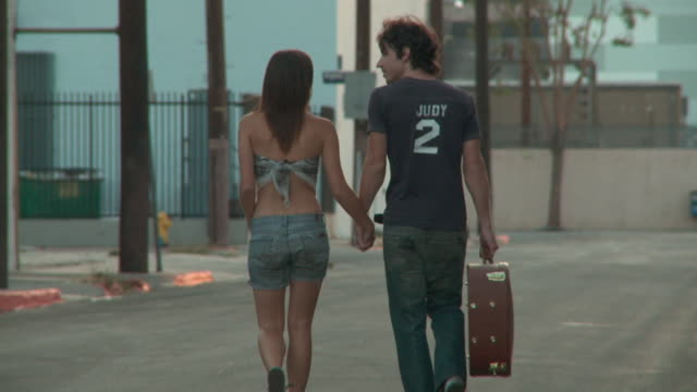 SLO MO, MS, Young couple walking on street, man carrying guitar, rear view, Los Angeles, California, USA