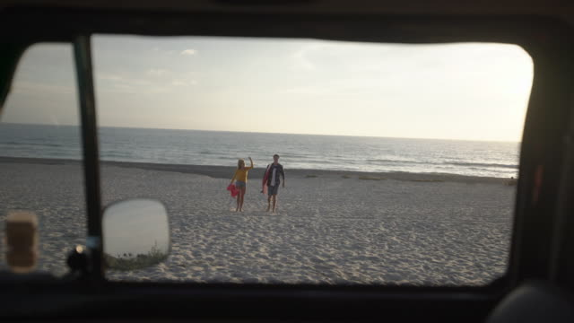 stockvideo's en b-roll-footage met ws young couple walking on the beach to their car - bus