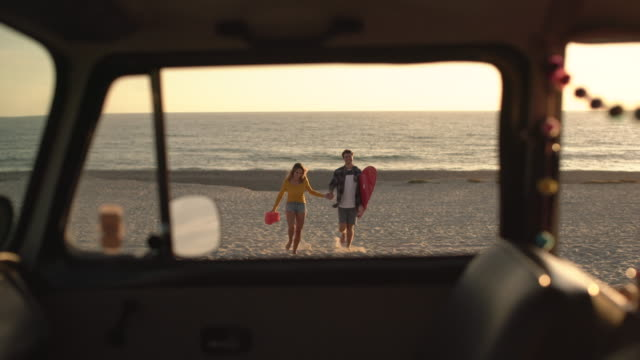 vídeos de stock e filmes b-roll de ws young couple walking on the beach together - acampar