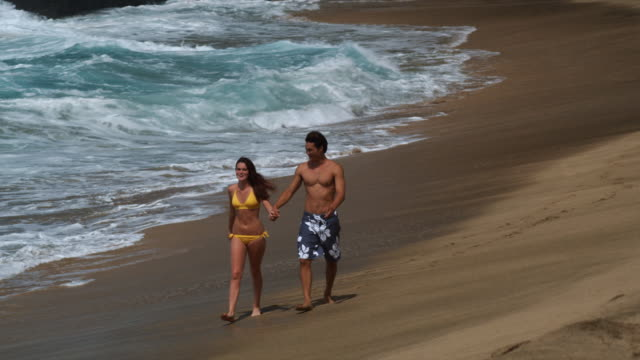 young couple walking on the beach - swimming shorts stock videos & royalty-free footage