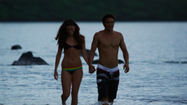 young couple walking on the beach - three quarter length stock videos & royalty-free footage