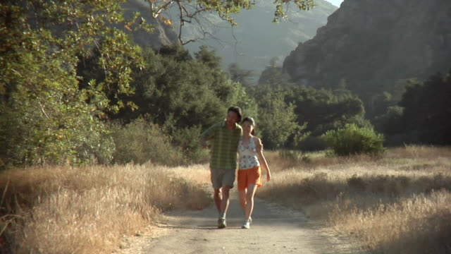 WS PAN Young couple walking on trail / Malibu Creek, California, USA