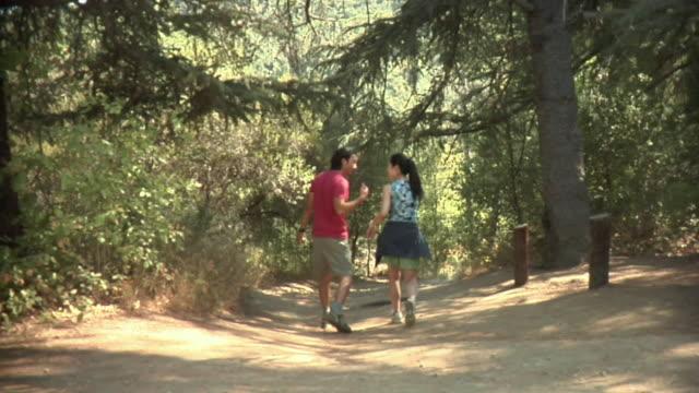 WS Young couple walking on trail / Malibu Creek, California, USA