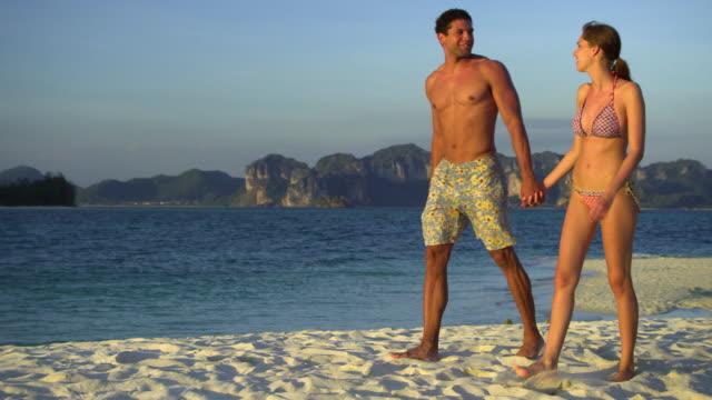 ws pan young couple walking on tropical beach, krabi, thailand - full length点の映像素材/bロール