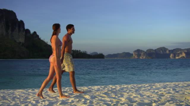 ws pan young couple walking on tropical beach, krabi, thailand - krabi province stock videos & royalty-free footage