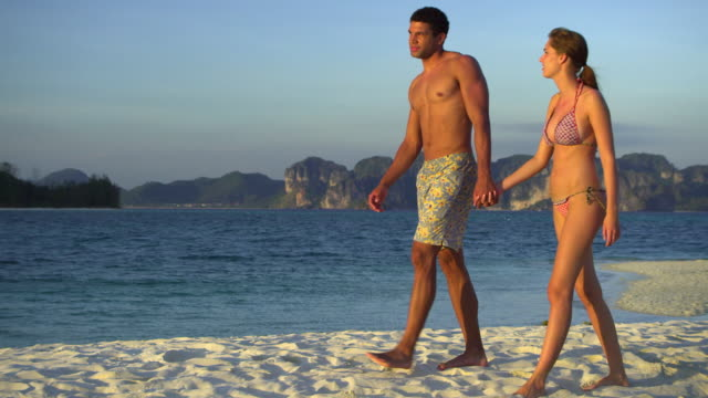 ws pan young couple walking on tropical beach, krabi, thailand - see other clips from this shoot 1459 stock videos and b-roll footage