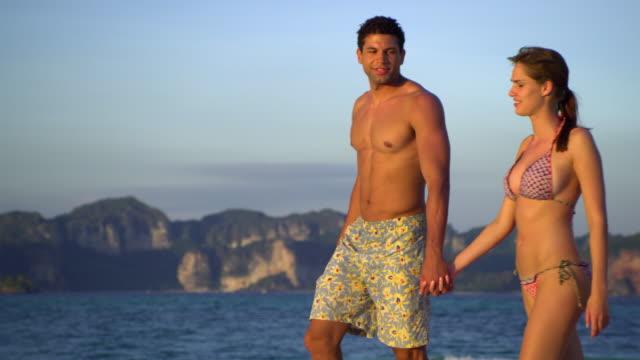 ms pan young couple walking on tropical beach, krabi, thailand - gemeinsam gehen stock-videos und b-roll-filmmaterial