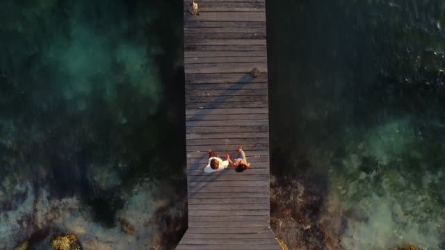 Young couple walking out to the end of pier shot follows them from above