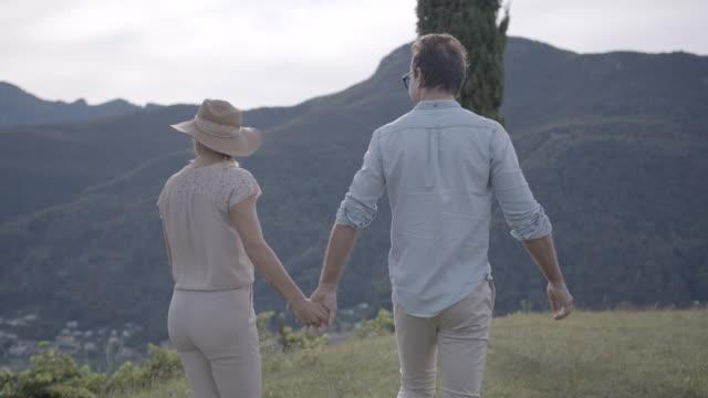 stockvideo's en b-roll-footage met young couple walking through  a vineyard near a lake - heteroseksueel koppel