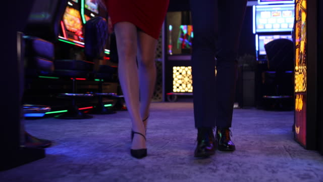 young couple walking through casino - casino stock videos & royalty-free footage