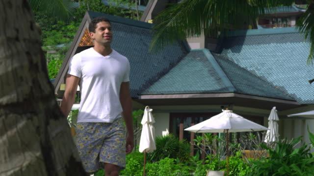 ms young couple walking through hotel resort in tropical surroundings, krabi, thailand - gemeinsam gehen stock-videos und b-roll-filmmaterial
