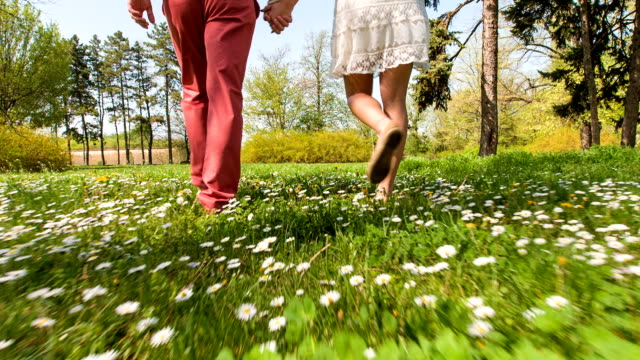 Young couple walking through park in springtime, low section