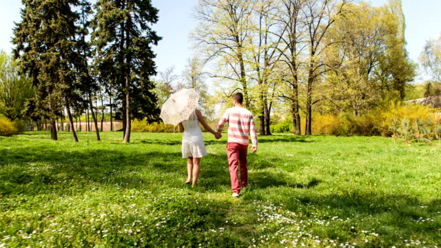 young couple walking through park in springtime - parasol stock videos & royalty-free footage