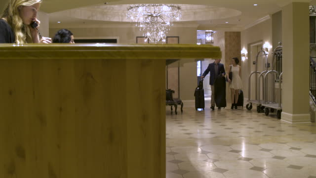 Young couple walking to a reception desk of a hotel and checking in
