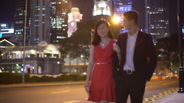 MS TS Young couple walking together at night.