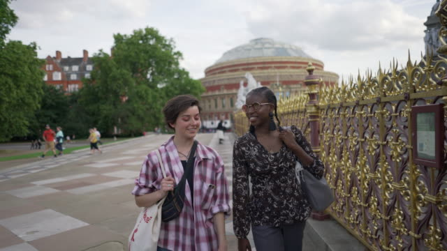 a young couple walking together chatting freely - royal albert hall stock videos & royalty-free footage