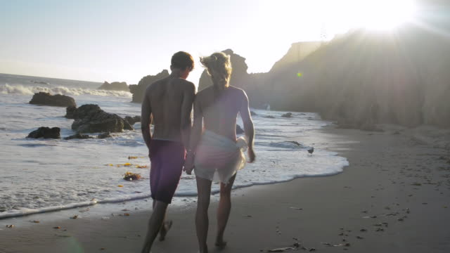 ws young couple walking together in beach surf at sunset / malibu, california, united states - malibu beach stock videos & royalty-free footage