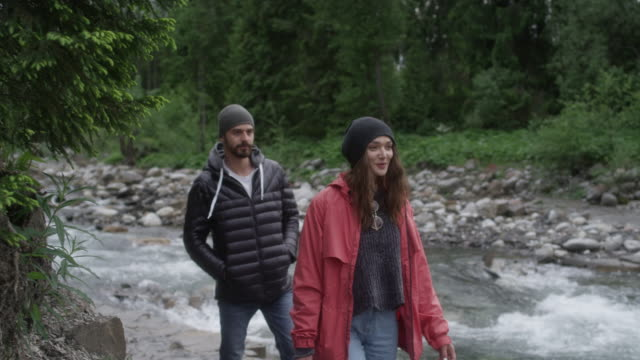 Young couple walking together in mountains. River in background