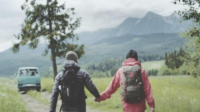 vídeos de stock, filmes e b-roll de casal jovem caminhando juntos nas montanhas - casal jovem