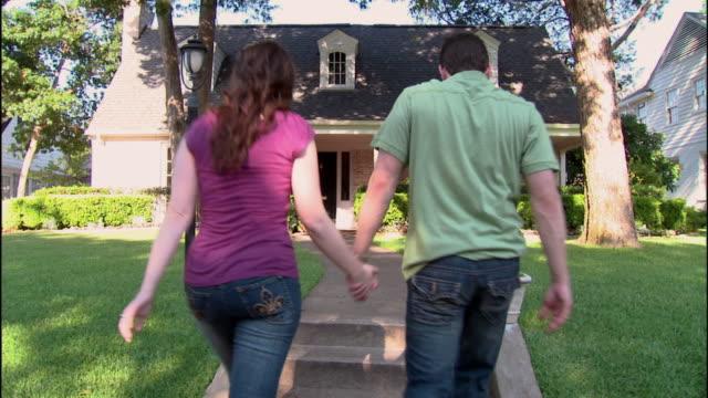 WS, Young couple walking towards brick suburban house, rear view, Dallas, Texas, USA