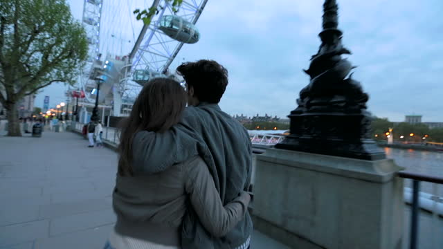 young couple walking towards the london eye share a kiss on the south bank. - millennium wheel stock videos & royalty-free footage