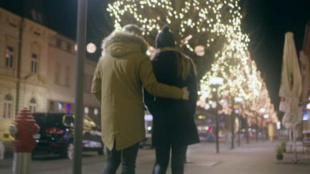 WS Young couple walking under Christmas lights
