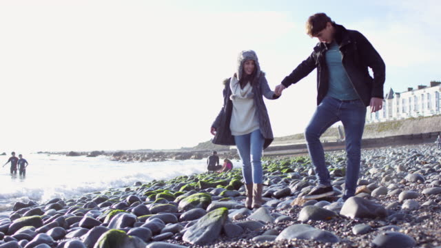 A young couple walking whilst holding hands on the beach at Porthmadog